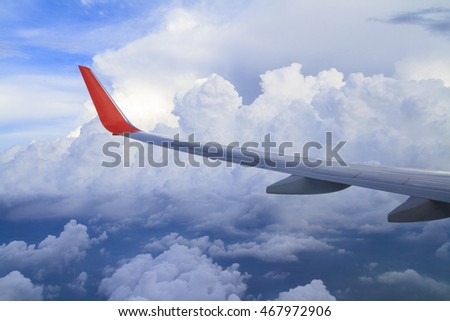 Flying wing of airplane on white puffy clouds and blue sky, view from an airplane window.