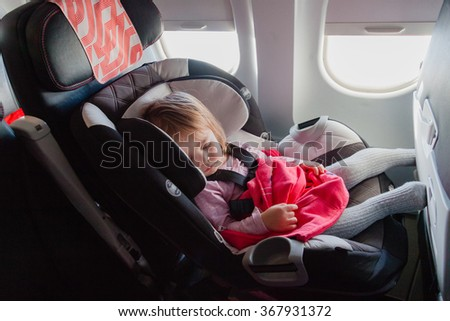 Flying with children: two year old baby sleeping in her own car seat setting on an ordinary seat on a commercial airliner. Concept photo of air travel with baby. Natural in-plane lightning conditions - stock photo