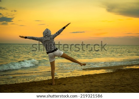 flying woman on the beach, sunset - stock photo