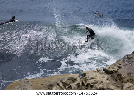 Foam and spray surrounds an surfer in central California.