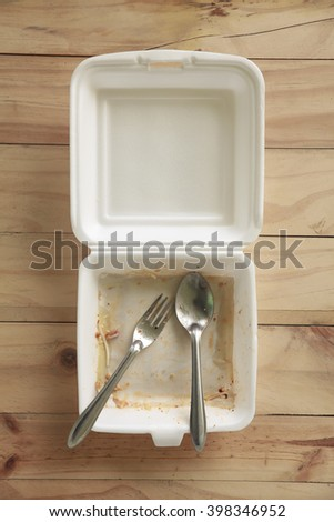 Foam boxes over eating on wooden table. - stock photo
