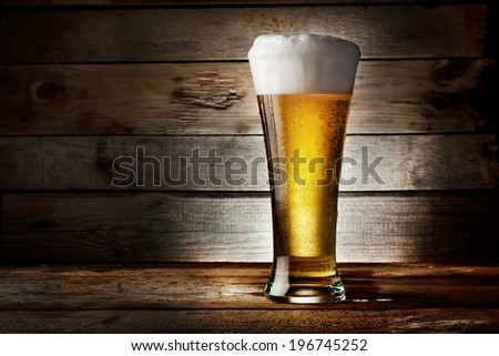 Foam glass of lager beer on a wooden background