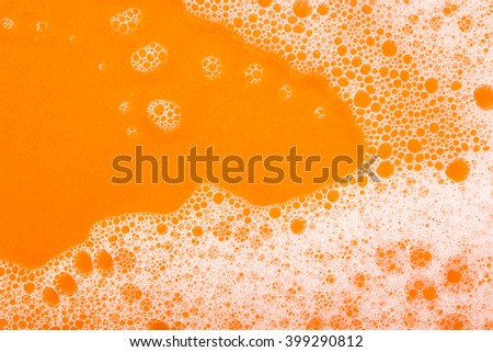 foam on orange background macro - stock photo