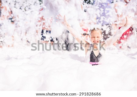 Foam Party on the beach. Cute little girl having fun and dancing. - stock photo
