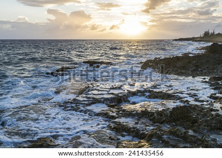 Foam settles around the famous Blow Holes on the south coast of Grand Cayman against the setting sun. - stock photo