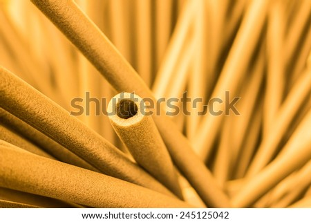 Foam tubes in the warehouse. In yellow tones - stock photo