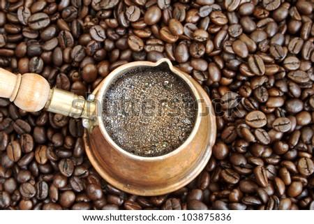 Foaming coffee in an arab copper coffee pot - stock photo