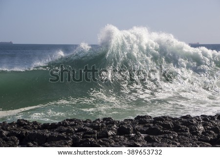 Foamy back wash from the Indian Ocean waves splashing high into the air against dark basalt rocks at Ocean Beach, Bunbury, Western Australia on a cold day in early winter are dramatically majestic. - stock photo