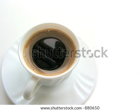 Foamy espresso coffee in a white cup with saucer on white background, top view, space for copy