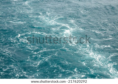 Foamy track on green sea behind the stern of the ship   - stock photo
