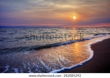 Foamy water crashing onto sandy beach shore at sunset with distant cliffs - stock photo