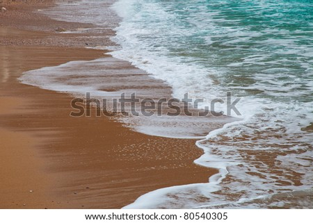 Foamy waves rolling to the sandy beach - stock photo