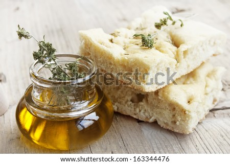 Focaccia italian bread slices with olive oil bottle placed over wooden table - stock photo