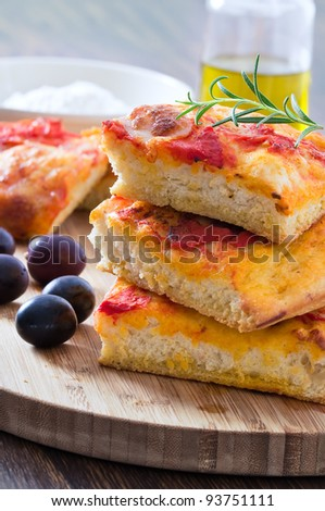 Focaccia with tomato and black olives. - stock photo