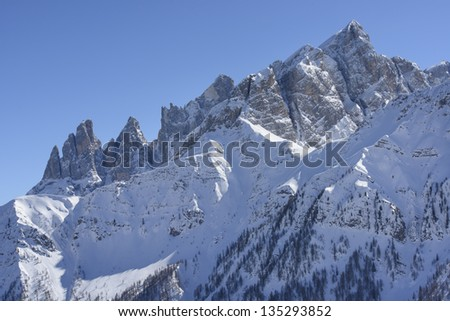 Focobon range in winter, Falcade; winter view of mountain range in Dolomites, shot under deep blue sky