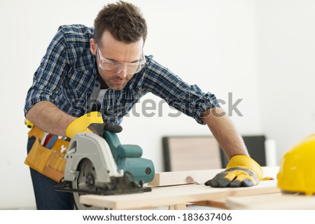 Focus carpenter sawing wood board - stock photo