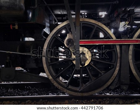 Focus detail of old steam train locomotive wheels on backlight - stock photo