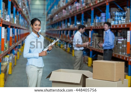 Focus of manager is smiling and posing during work in a warehouse
