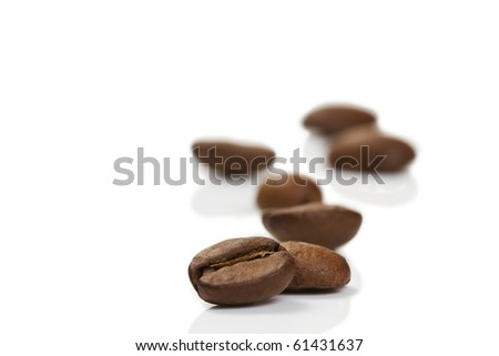 focus on a coffee bean in front of others on white background - stock photo