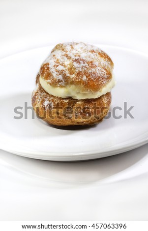 Focus on a cream puff and sugar on a porcelain plate - stock photo