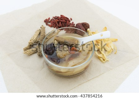 Focus on a glass bowl of Chinese herbal nourishing soup.  Blur vision of  natural dried ingredients namely solomonseal rhizome, wolfberry, codnopsis pilosulae radix and red dates at the background.