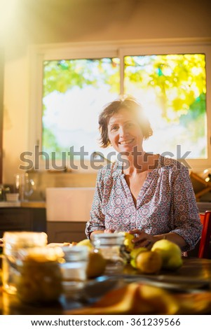 Focus on a smiling real woman in a luminous kitchen sitting at a wooden table with fruits and utensils around her, to make rustic and old fashioned jar of fruits. Blur background. Shot with flare - stock photo