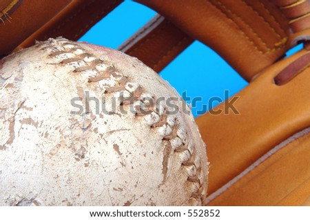 focus on a well worn softball with a fade into a baseball glove - stock photo