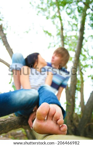Focus on barefoot leg fingers Pretty young couple sitting kissing and hugging on tree trunk, her bare feet in foreground on sky, summer or spring trees background Empty Copy space for inscription  - stock photo