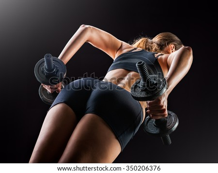 Focus on black shorts. Dark contrast image of fitness woman's back and buttocks. She is training - doing squats with dumbbells on black background in studio. - stock photo