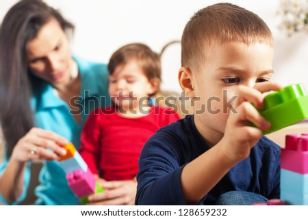 Focus on boy playing with cubes with mother and sister in background - stock photo