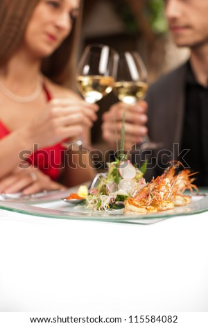 Focus on fresh prawns on plate with couple toasting in background. - stock photo