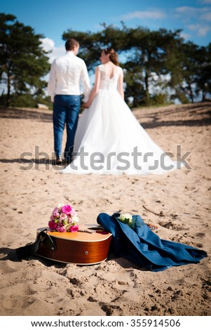 Focus on guitar, wedding bouquet and the groom's jacket, lying in the sand. Bride and groom walking away hand in hand - stock photo