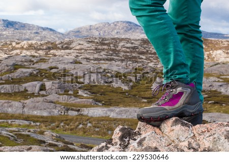 Focus on legs of a female model wearing purple and grey hiking boots with rocky landscape in the background. Scotland, UK. - stock photo