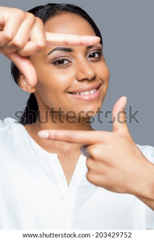 Focus on me! Portrait of playful young African woman gesturing finger frame and looing through it with smile while standing against grey background - stock photo