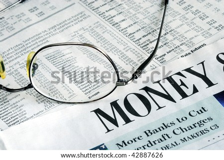 Focus on Money Investing from a newspaper - stock photo