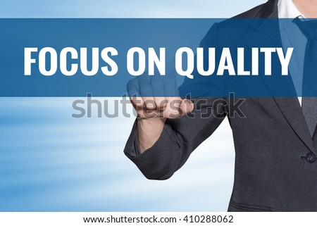 Focus On Quality word Business man touching on blue virtual screen - stock photo