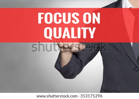 Focus On Quality word Business man touching on red tab virtual screen for business concept - stock photo