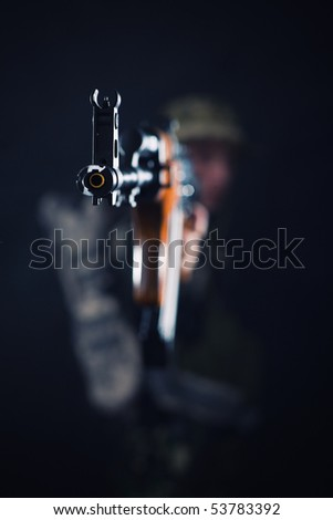Focus on shooting Kalashnikov being held by soldier.
