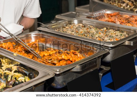 Focus on Steamer Tray Containing Skewers of Grilled Shrimp in Row of Buffet Offerings at Restaurant or Food Festival - stock photo