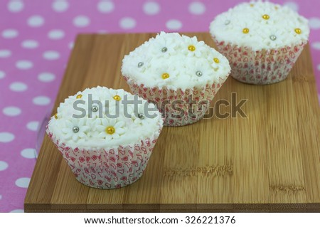 Focus on the front most cupcake and blurring cakes behind. On wooden board and pink polka dots background. Beautiful decorative fondant topping of white floral with golden and silver edible beads.   - stock photo