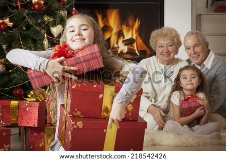 Focus on the happy little girl getting Christmas presents   - stock photo