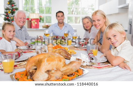 Focus on the roast turkey in front of family at chrismas dinner - stock photo