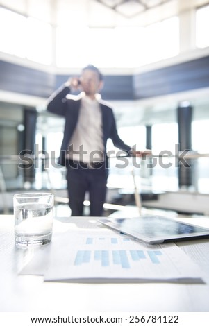 Focus on the things on the table. Blurred man on background. - stock photo