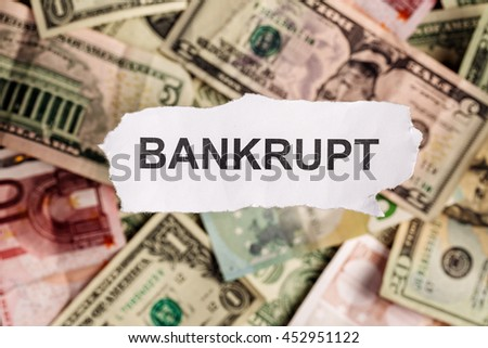 Focus on the word BANKRUPT on piece of torn white paper with blur banknotes currency as a background. Concepts of finance and business. - stock photo