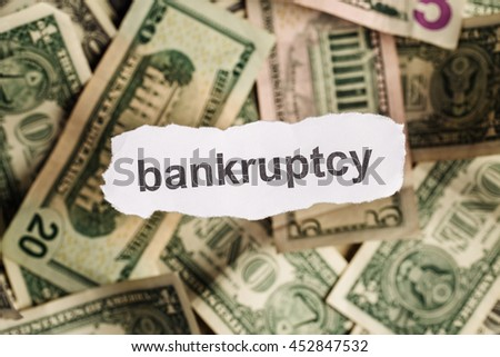 Focus on the word BANKRUPTCY on piece of torn white paper with blur banknotes currency as a background. Concepts of finance and business.