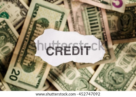 Focus on the word CREDIT on piece of torn white paper with blur banknotes currency as a background. Concepts of finance and business. - stock photo