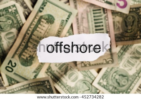 Focus on the word OFFSHORE on piece of torn white paper with USD dollars currency as a background. Concepts of security and business.