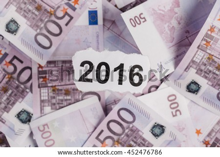 Focus on the words 2016 on piece of torn white paper with EURO currency as a background. Concepts of investment and business. - stock photo