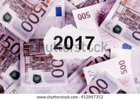 Focus on the words 2017  on piece of torn white paper with EURO currency as a background. Concepts of investment and business. - stock photo