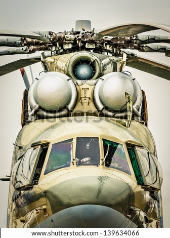 Focus on windows of cockpit and propeller of russian military helicopter, gray sky in background. Army air transport in Russia. Front view of chopper outdoors. Modern, beautifully designed helicopter. - stock photo